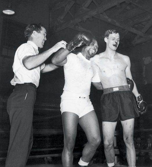 George Plimpton, right, after a boxing match with Archie Moore at Stillman's Gym, New York City, 1959; Ezra Bowen, the <i>Sports Illustrated</i> editor who acted as referee, is at left. 'Quite visible are the effects Archie Moore left on the author'